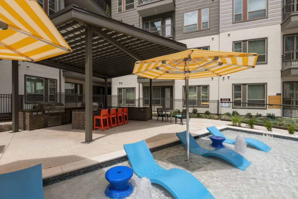 The main courtyard features a sleek resort-inspired pool with a tanning ledge, a fire feature, and grilling stations - Unwind in Style Every Weekend